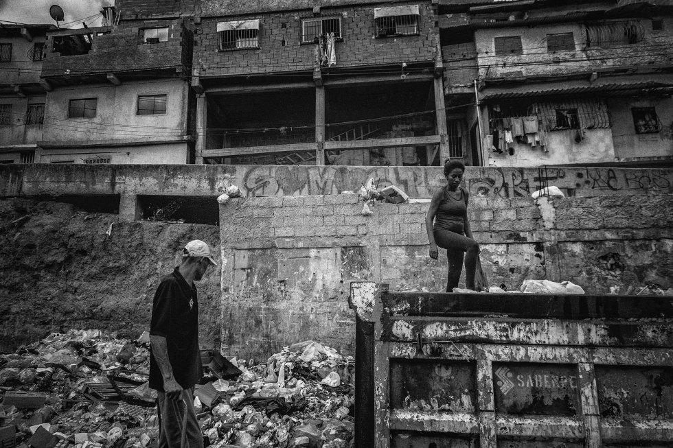 Una pareja rebusca en la basura en el barrio de Petare.