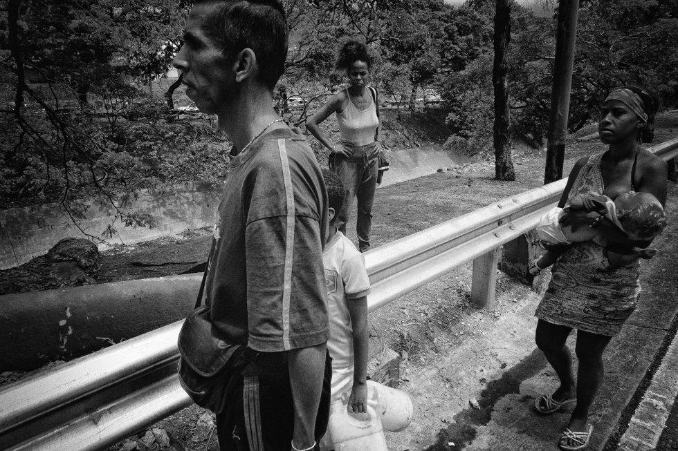 Una familia recoge agua de un cauce cercano a la autopista Francisco Fajardo, en Caracas.