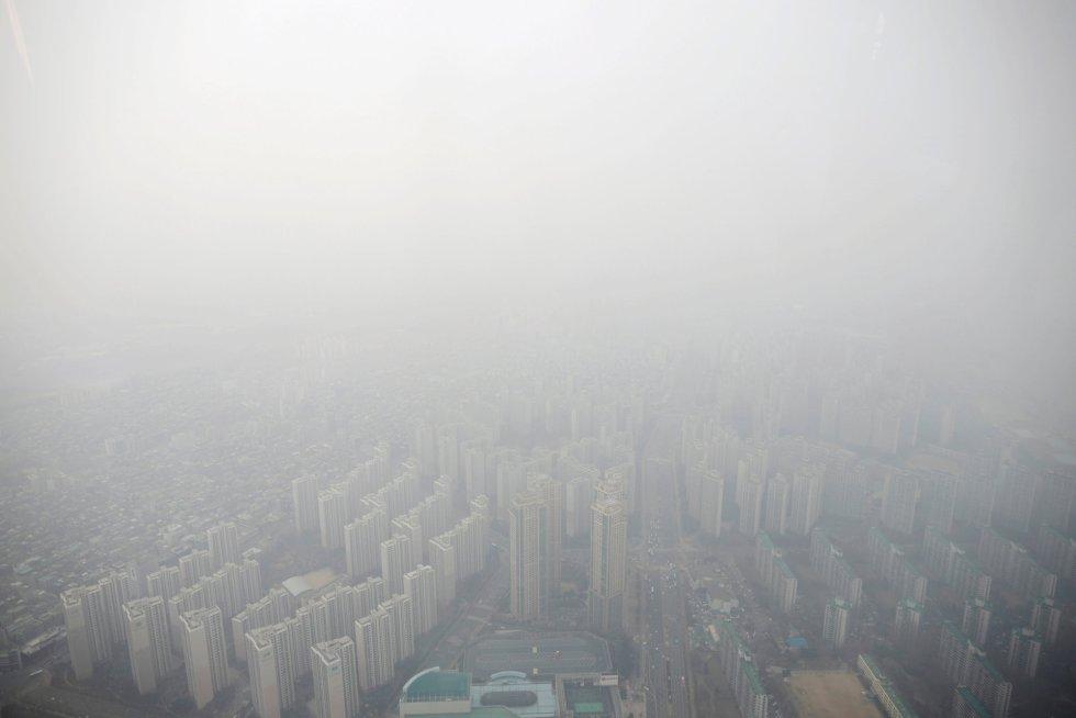 """O mais negativo é que os diferentes estudos científicos analisados indicam que os países não estão se movendo nessa direção. A sexta edição do GEO alerta que as projeções indicam """"que os avanços são muito lentos para atingir os objetivos, ou que eles até progridem na direção errada"""". Na imagem, edifícios envoltos por uma nuvem de poluição em Seul (Coréia do Sul), em 6 de março de 2019."""