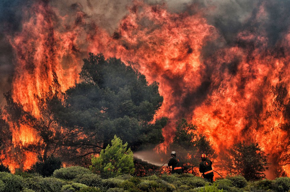 O problema da mudança climática - para muitos especialistas, o grande desafio da humanidade para este século - atravessa todo o relatório da ONU. Na imagem, bombeiros tentam apagar um incêndio na aldeia grega de Kineta, em 24 de julho de 2018.