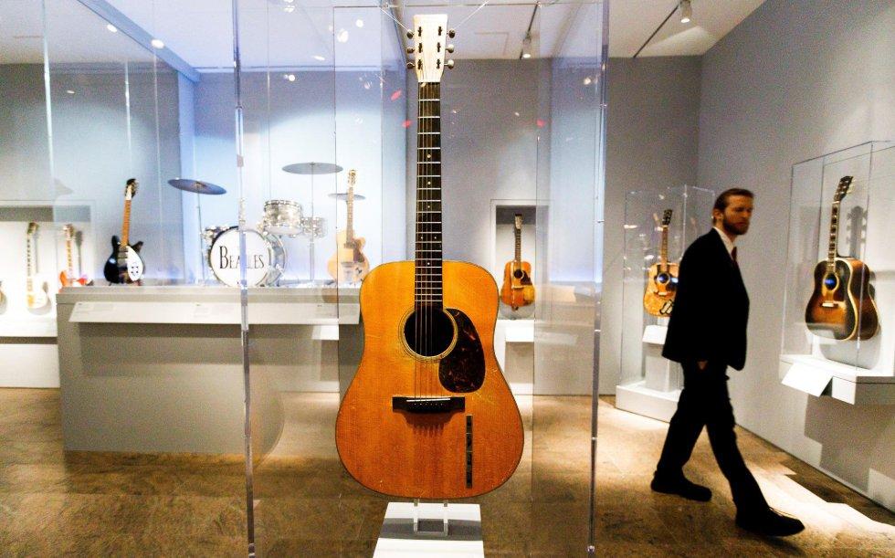 Um visitante observa uma guitarra tocada por Elvis Presley (centro) junto com a bateria de Ringo Star (à esquerda).