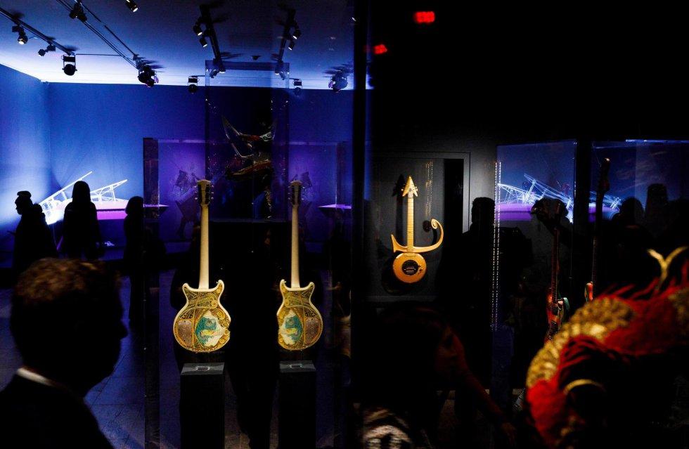Várias pessoas observam as guitarras de Steve Miller (à esquerda) e Prince (à direita), junto com um piano usado por Lady Gaga (ao fundo) durante a pré-estréia da exposição 'Play It Loud: Instruments of Rock & Roll'.