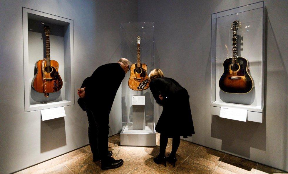 Duas pessoas observam a guitarra de Buddy Holly (centro) junto com as de Wanda Jackson (à esquerda) e Don Everly (à direita), que fazem parte da exposição 'Play It Loud: Instruments of Rock & Roll'.