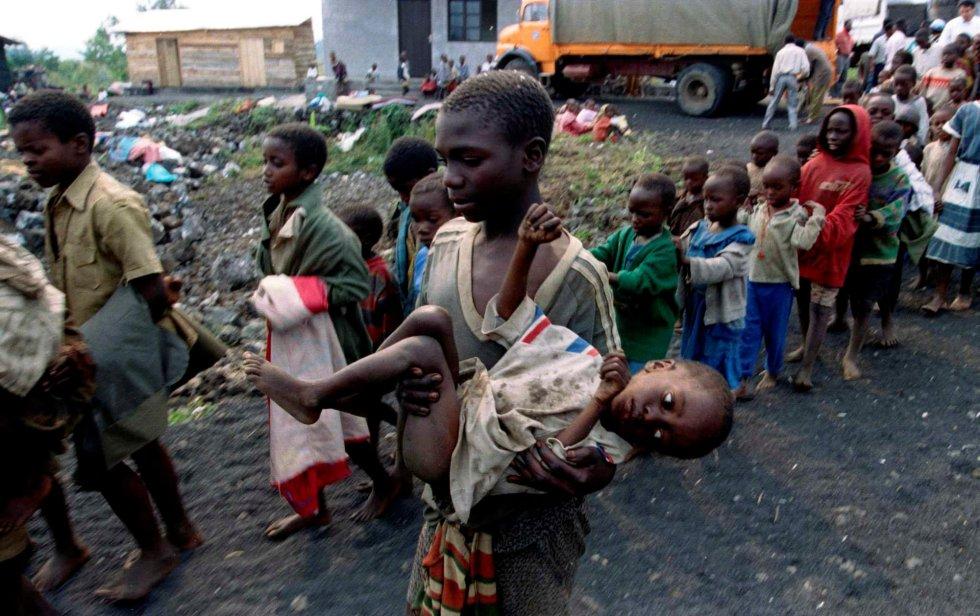 Un niño traslada en brazos a otro menor, desfallecido, a su llegada a un orfanato cerca de Goma, antiguo Zaire, el 19 de julio de 1994.