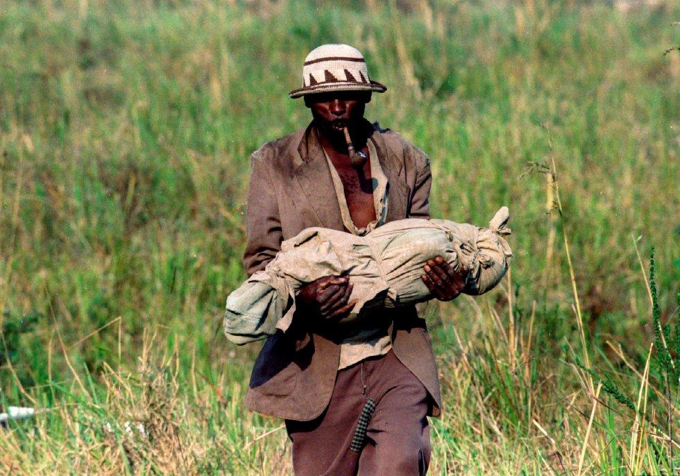 Un refugiado se dirige a una fosa común con el cuerpo de su hijo, un bebé muerto por cólera, el 29 de julio de 1994.