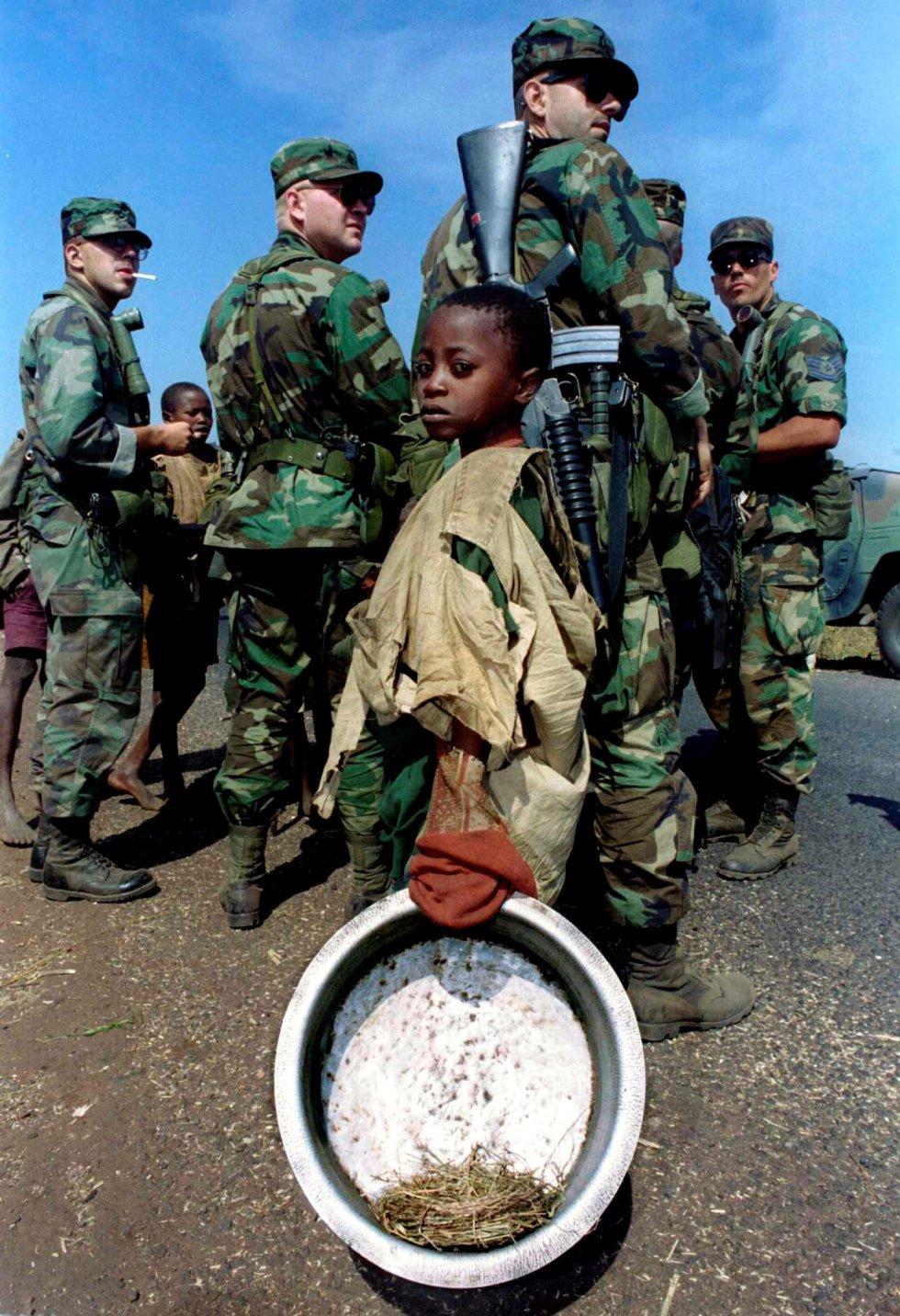 Un niño ruandés espera para recoger agua frente a un grupo de soldados de Estados Unidos en el campo de refugiados de Kibumba (Tanzania), el 2 de agosto de 1994.