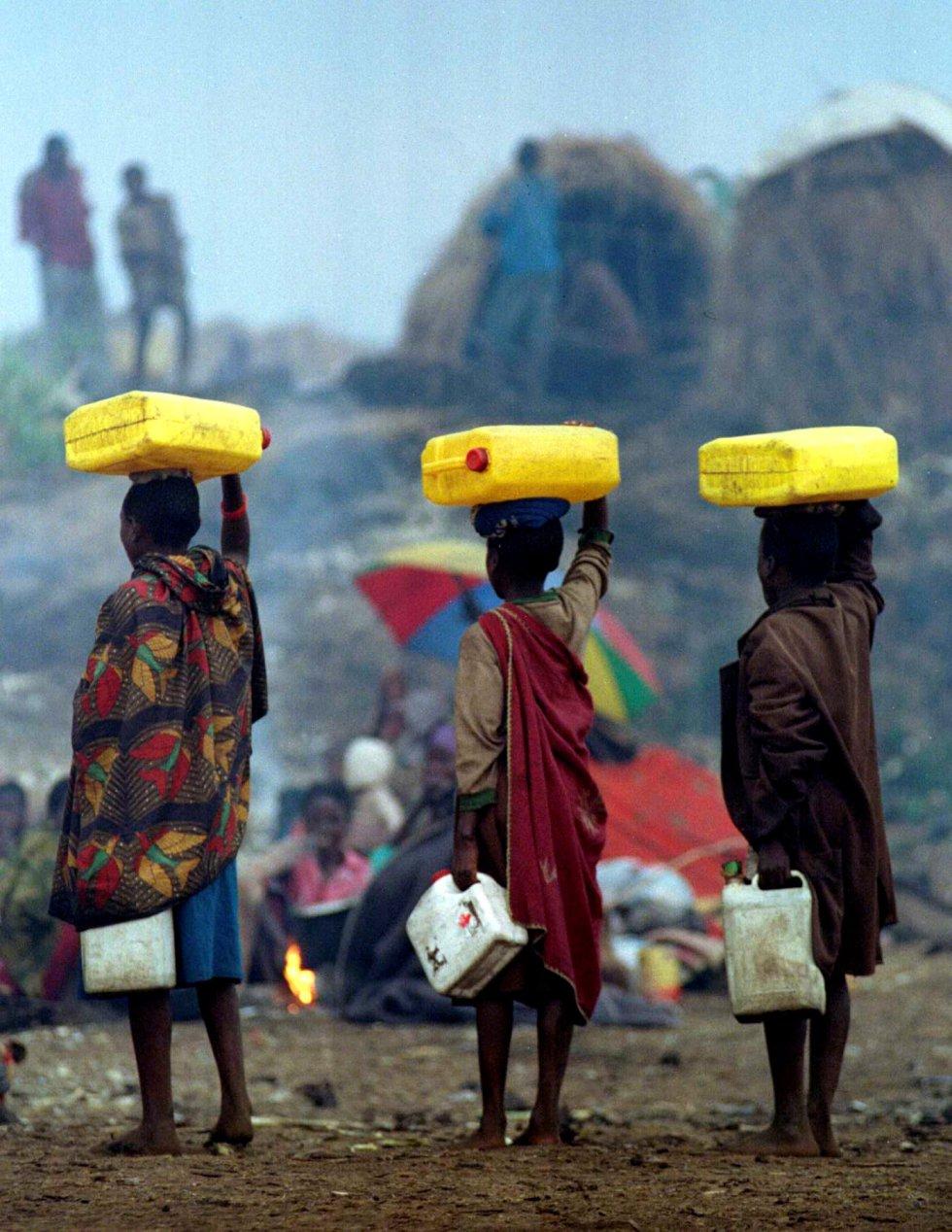 Tres jóvenes refugiados transportan bidones de agua distribuidos por militares franceses en el campamento de refugiados de Mugunga, cerca de Goma, el 13 de agosto de 1994.