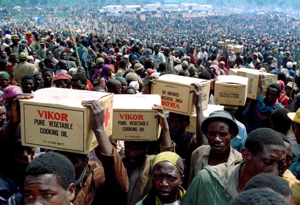 Refugiados ruandeses transportan alimentos suministrados por la Cruz Roja, el 28 de julio de 1994.