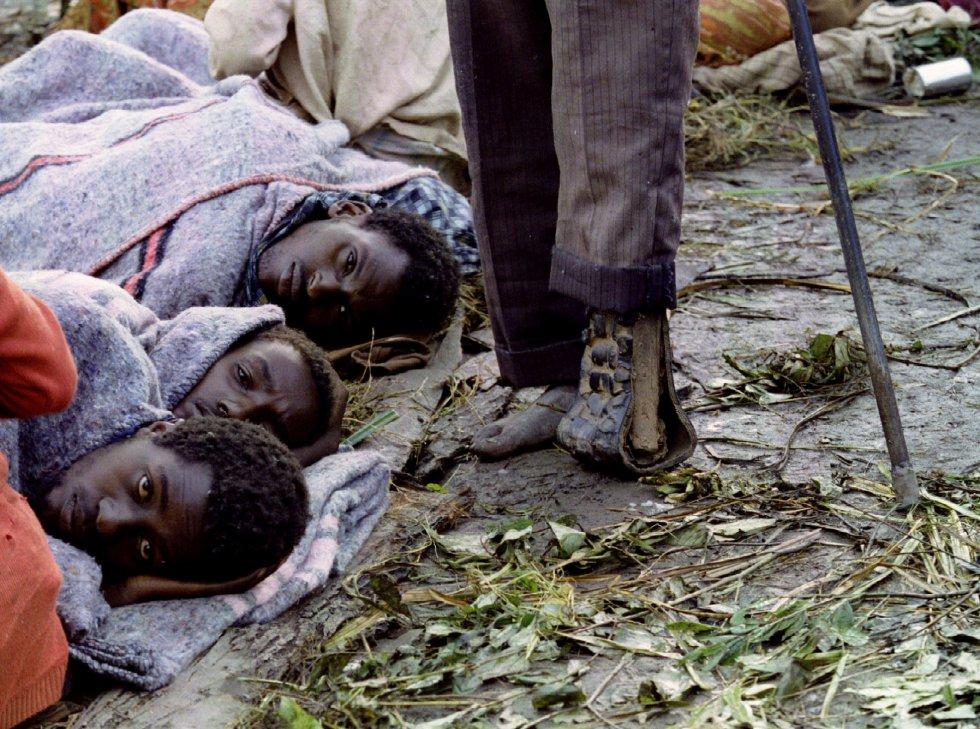Los victoriosos tutsis del FPR formaron un Gobierno en Kigali e instaron a los refugiados a regresar al país, pero al mismo tiempo pidieron a la comunidad internacional la formación de un tribunal para juzgar a los hutus por genocidio. En la imagen, tres refugiados tutsis se acurrucan para protegerse del frío y la humedad mientras pasa junto a ellos un hombre con la pierna amputada, en un campamento al sur de Ruanda, el 20 de mayo de 1994.