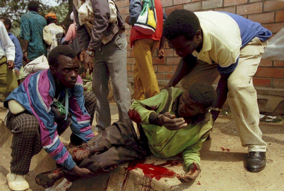 El mayor genocidio registrado en el mundo, según la ONU, comenzó la noche del 6 de abril de 1994, horas después de que el presidente del país, Juvenal Habyarimana, muriera tras ser alcanzado por dos misiles el avión en el que se disponía a aterrizar en el aeropuerto de Kigali. En la imagen, varias personas ayudan a levantarse a un herido por los disparos de los miembros del Frente Patriótico de Ruanda en un campamento de Kigali, el 1 de julio de 1994.