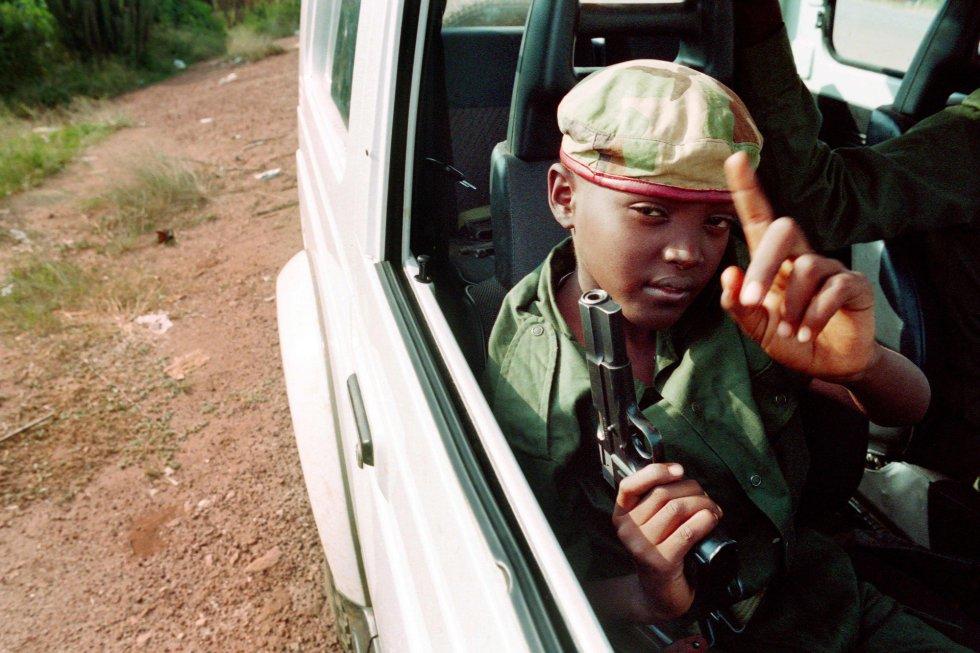Un niño armado con una pistola patrulla las calle de Kigali en un automóvil junto a partidarios del Frente Patriótico de Ruanda, el 9 de junio de 1994.