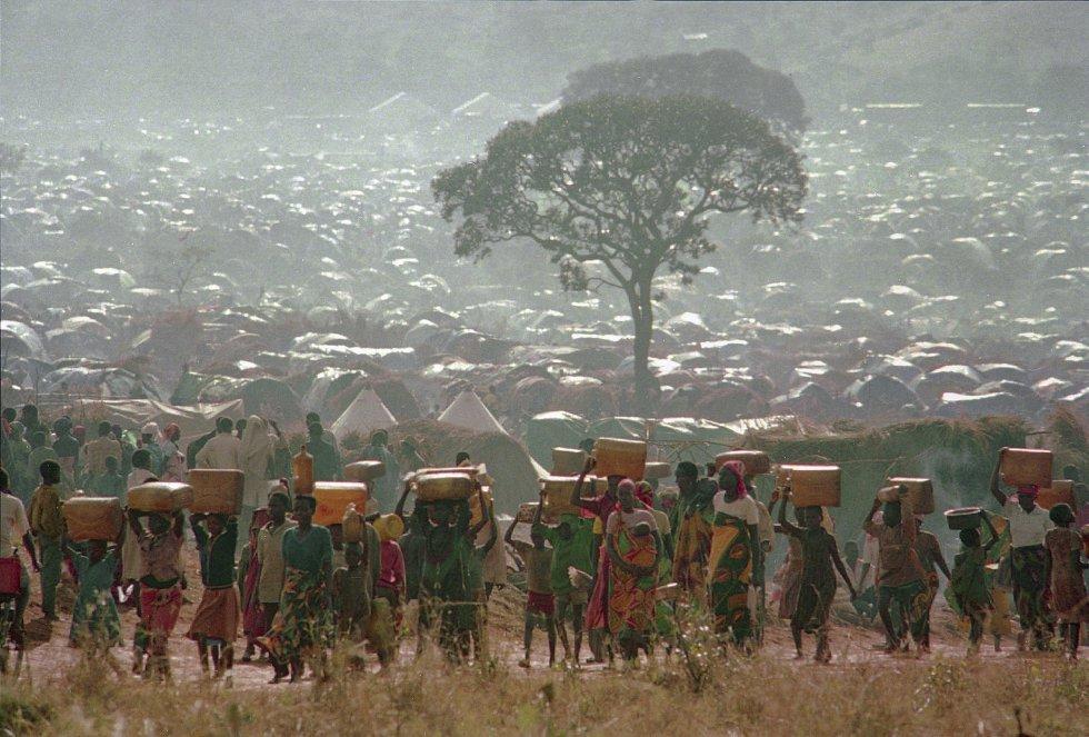 En cuanto se corrió la voz de la muerte de Habyarimana, los hutus comenzaron a matar a tutsis y miembros moderados de su propia etnia: hombres, mujeres, niños y ancianos fueron masacrados a tiros y machetazos. En la imagen, desplazados ruandeses, que huían del baño de sangre, transportan contenedores de agua a sus chozas en el campamento de refugiados de Benaco en Tanzania, cerca de la frontera con Ruanda, el 17 de mayo de 1994.