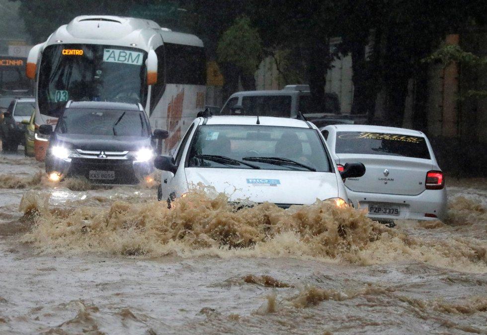 Las corrientes de agua producidas por las lluvias que caen sin parar desde hace más de 14 horas han arrastrado innumerables vehículos y causado inundaciones en calles y túneles de la ciudad. En la foto, un atasco en mitad de las inundaciones en una calle Jardín Botánico de Río de Janeiro.