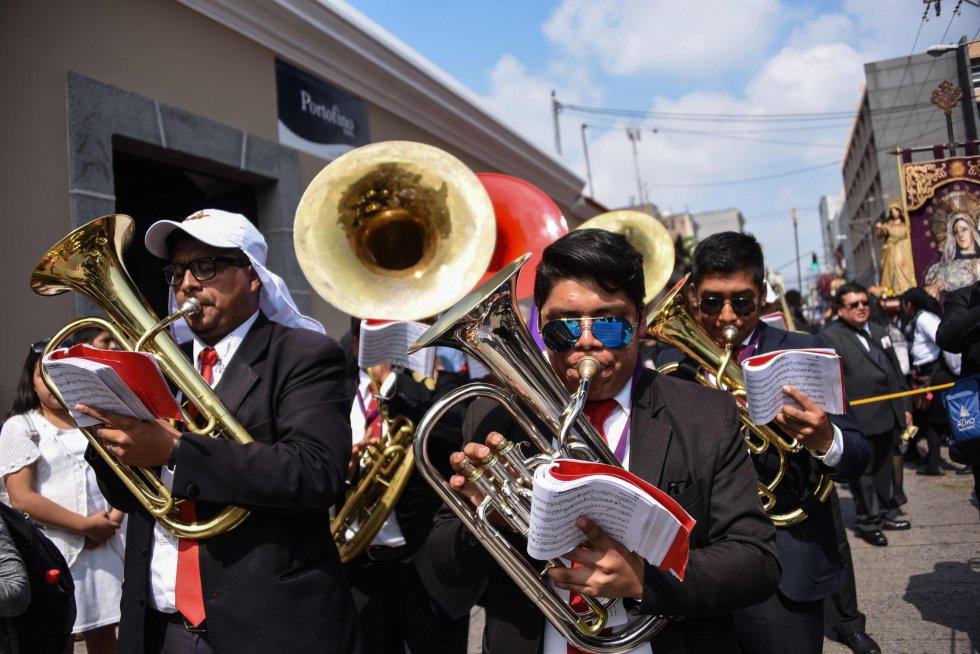 Fieles católicos participan con sus instrumentos en la procesión de Jesús de Nazaret en Ciudad de Guatemala, el 16 de abril de 2019.