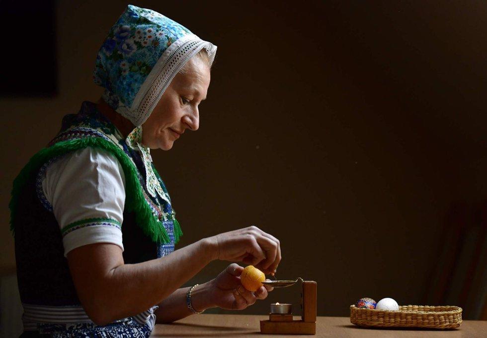 Una mujer de la minoria sorbia decora un tradicinal huevo de Pascua en Schleife (Alemania), el 18 de abril de 2019.