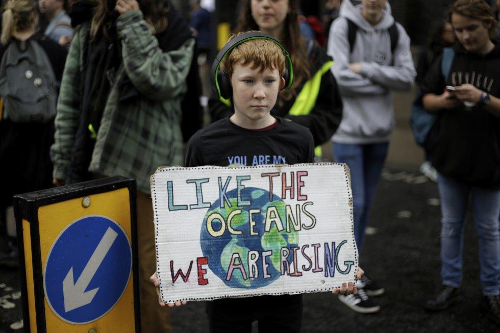 El movimiento XR anunció que el jueves 25 de abril pondrá fin a sus bloqueos en Londres, tras once días de acciones para reclamar un 'estado de emergencia ecológico'. En la foto, un joven manifestante sostiene una pancarta mientras bloquean una carretera en el centro de Londres, miércoles 24 de abril de 2019.