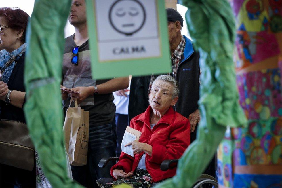 Una mujer acude a votar en silla de ruedas, con su papeleta en la mano, en un colegio de Valencia.