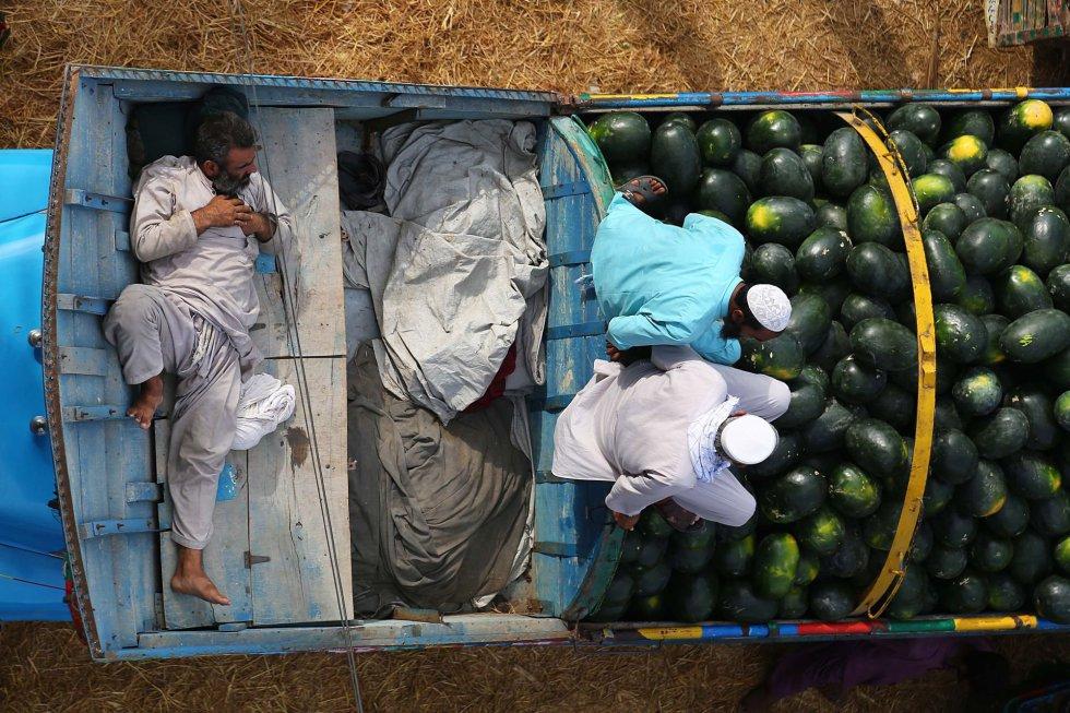 Tres hombres venden sandías en un mercado de fruta y verdura durante el mes sagrado de ayuno en la religión musulmana, el 7 de mayo de 2019 en Karachi (Pakistán). El Ramadán es uno de los doce meses islámicos, que se rigen por el calendario lunar, y no el solar.