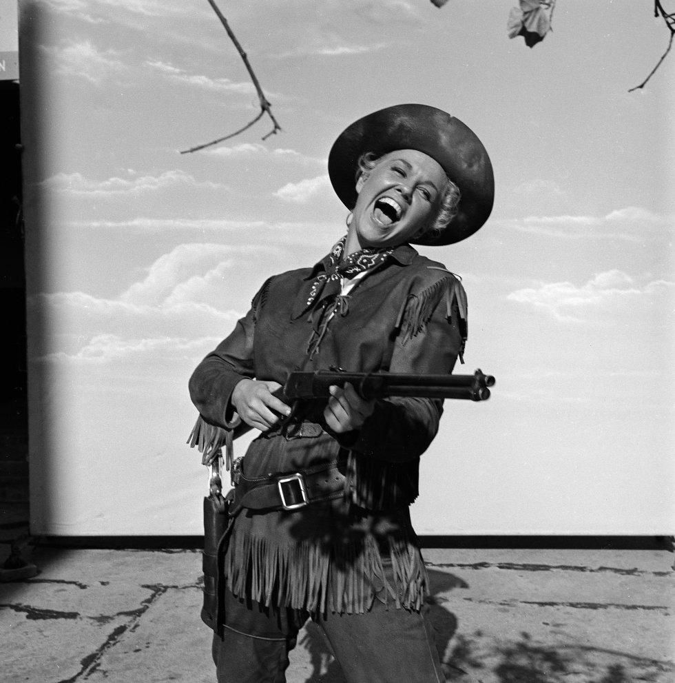 La actriz Doris Day, disfrazada de vaquera, apunta un rifle frente a un fondo de cielo con nubes, durante una sesión de fotos para promocionar la película musical 'Calamity Jane', dirigida por David Butler, en 1953.