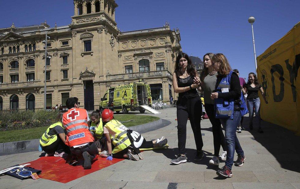 Profesionales sanitarios atienden a los heridos en el exterior del Victoria Eugenia, con el teatro al fondo.