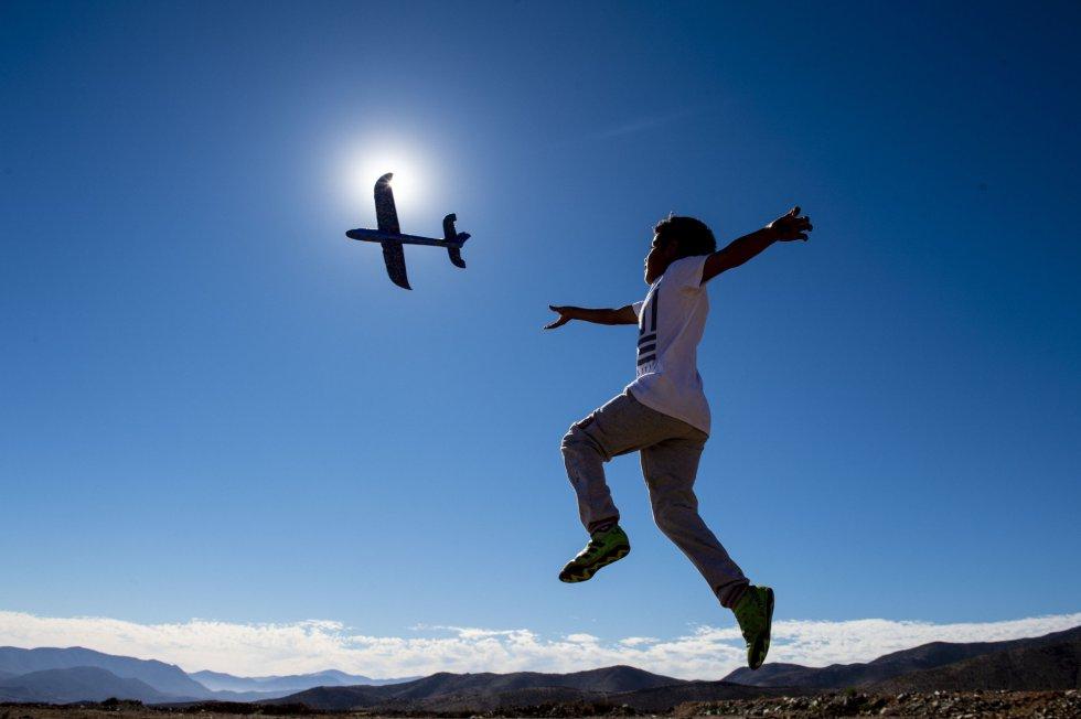 Un niño juega con un avión en el desierto de Atacama, desde donde se ha visto el eclipse.