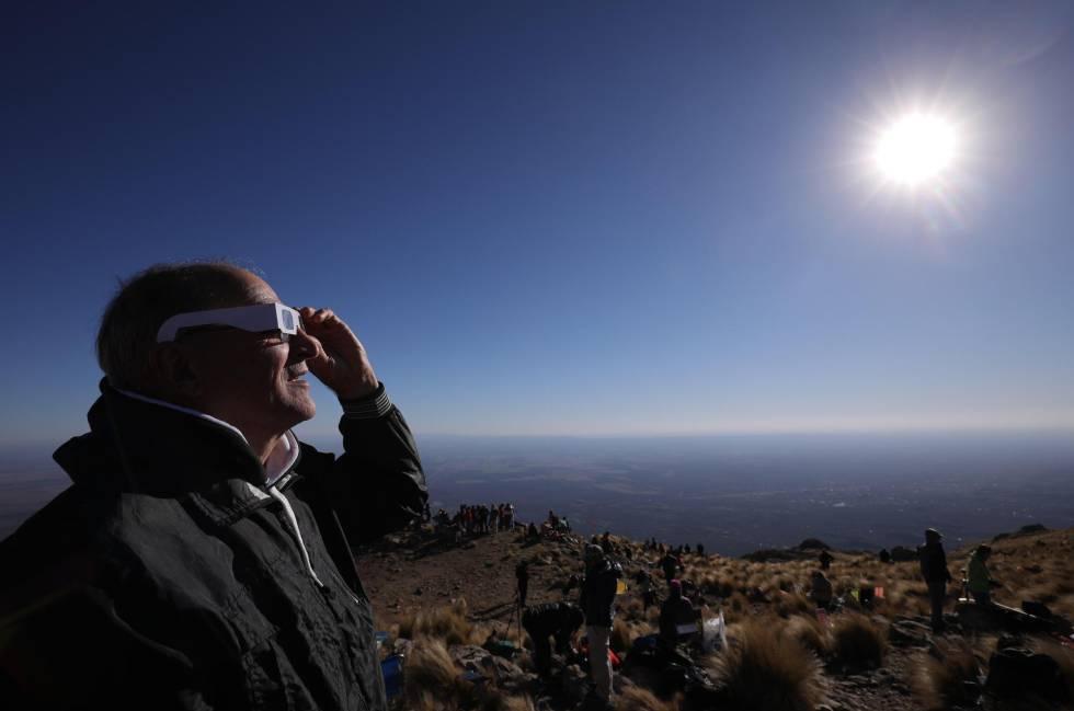 Un hombre mira el sol con anteojos especiales antes del eclipse.