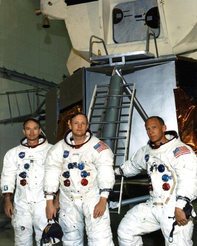 Desde la izquierda, los astronautas Michael Collins, Neil A. Armstrong y Edwin E. Aldrin posan junto a una maqueta del módulo lunar en el área del edificio de entrenamiento de tripulación de vuelo, el 19 de junio de 1969.
