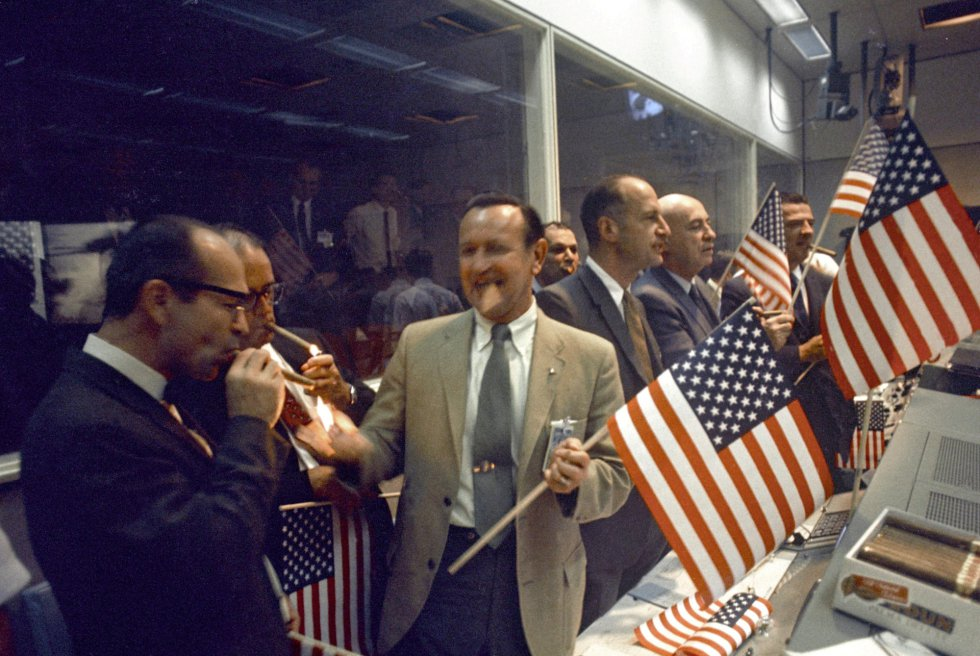 Miembros de la NASA y del Centro de Naves Tripuladas (MSC) celebran junto a los controladores aéreos el éxito de la misión del Apolo 11, en el Centro de Control de Misiones de la NASA en Houston, Texas, el 24 de julio de 1969.