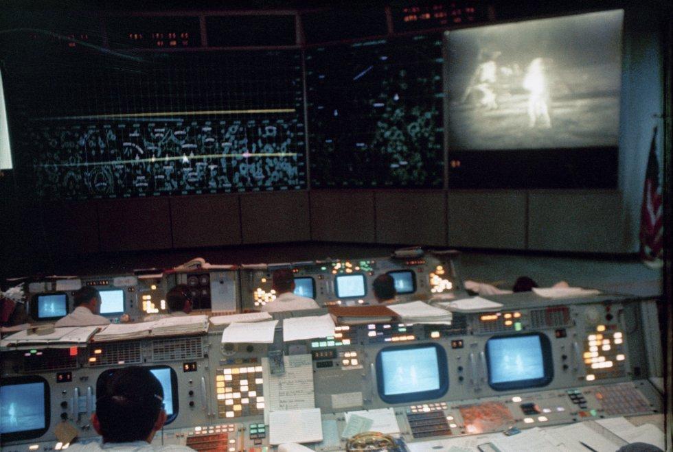 Los controladores aéreos trabajan en la sala de control de operaciones en Houston, Texas, durante la actividad del 'Apolo 11' en la Luna. El monitor de televisión muestra a los astronautas Neil Armstrong y Buzz Aldrin en la superficie lunar, el 20 de julio de 1969.