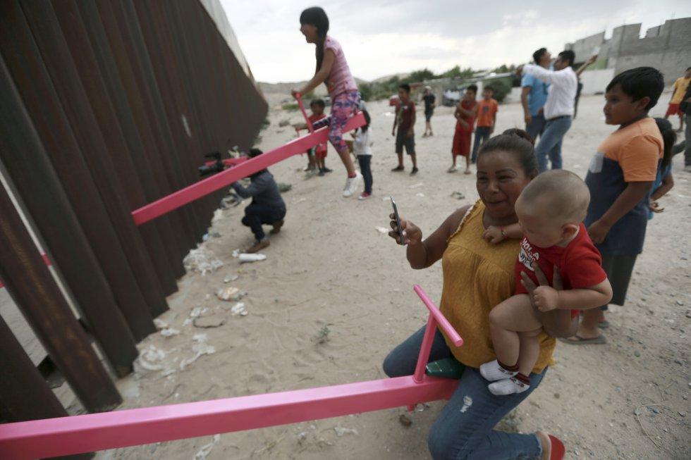 El Gobierno mexicano afirma que sin su cooperación llegarían este año 250.000 migrantes sin papeles a territorio estadounidense. En la imagen, una madre y su hijo juegan junto a la valla en Ciudad Juárez.