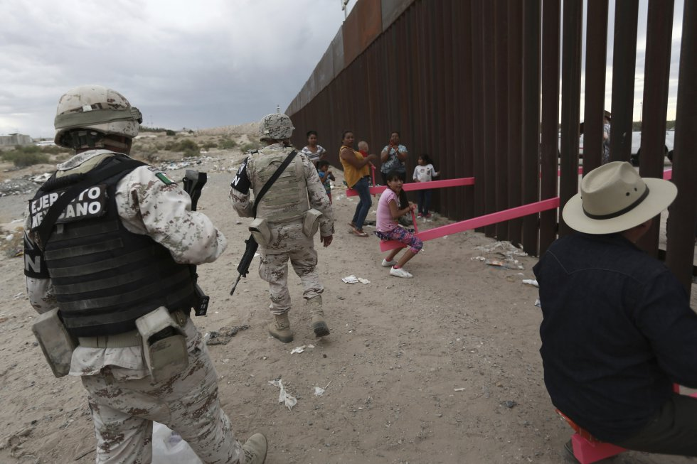Miembros de la policía militar mexicana patrullan entre los niños y los adultos que acuden a la valla fronteriza para jugar, en Ciudad Juárez.
