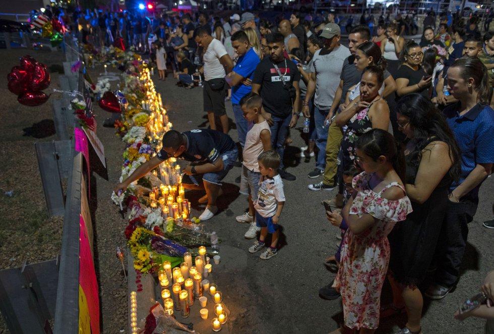 Las personas se reúnen en un memorial improvisado para las víctimas del tiroteo masivo del sábado en un complejo comercial en El Paso, Texas, el 4 de agosto de 2019.