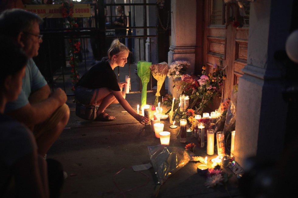 Varias personas dejan flores y velas en la entrada del bar Ned Peppers en el Distrito de Oregon, el 4 de agosto de 2019, en Dayton, Ohio.