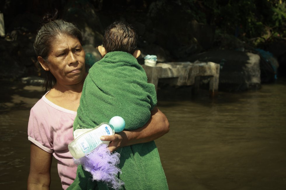 Una mujer de la comunidad La Montañita se dirige a lavar su ropa y aprovecha a bañar a su nieto en la orilla frente a la Isla Filipinas, Granada.rn