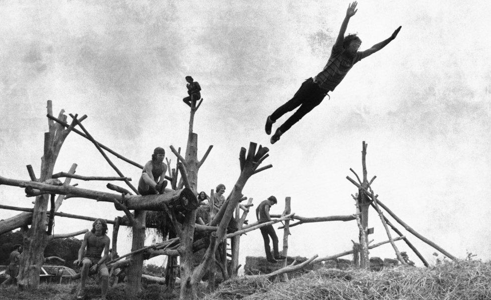 """Para algunos estadounidenses, el festival fundamental de """"paz y música """" hace 50 años fue un momento inspirador de comunidad contracultural y de libre pensamiento juvenil. Para otros, fue una muestra escandalosa de decadencia moral e indulgencia en tiempos de guerra. En cualquier caso, el festival de Woodstock, en el que participaron artistas como Jimi Hendrix, Janis Joplin o Neil Young, es considerado como el más importante de la historia de la música y el origen de una profunda transformación en la cultura y sociedad de la época. En la imagen, asistentes saltan sobre un montón de heno durante el festival celebrado en Bethel, Nueva York (EE UU)."""