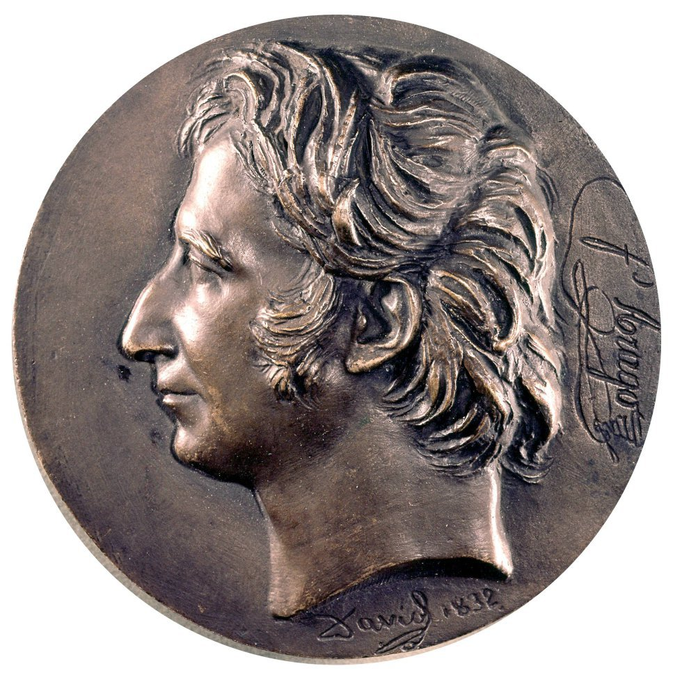 Daguerre habla con François Aragó (1786-1853), un político francés, con la intención de regalar al mundo la fotografía, el invento que reemplazaría al dibujo. En la época de la ilustración el objetivo era compartir el conocimiento, por lo tanto, Aragó convenció al gobierno francés para comprar la patente. En la imagen, medallón con el busto de Aragó.