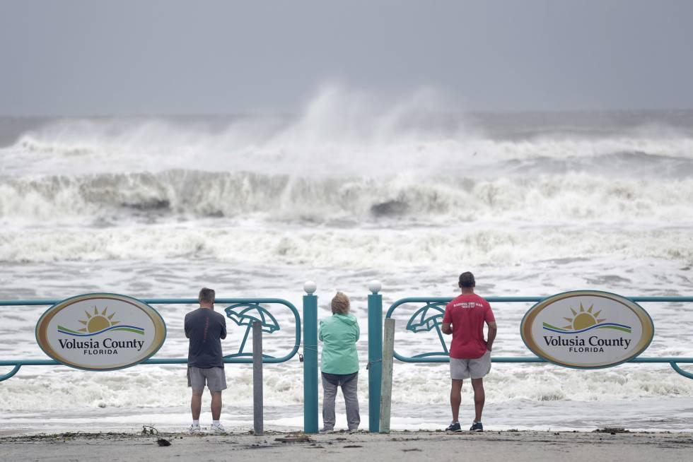 Turistas observam força das ondas na costa de Ormond Beach, na Flórida.
