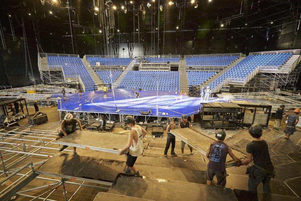 """Un campo de 40 metros de largo. Dos tribunas y más de 3.000 asientos en las gradas. 47 artistas de 19 nacionalidades. Más de un centenar de cambios de vestuario. Dos actos de 45 minutos más un intervalo de 25. 267 toneladas de equipamiento que se han trasladado desde la sede principal del circo, en Canadá, hasta el otro lado del Atlántico. Estas son las cifras de un espectáculo único por el que también se ha hecho un despliegue excepcional: """"El Cirque du Soleil trata de garantizar la mejor experiencia posible para el espectador, una ambición compartida con LaLiga para tratar de ofrecer el mejor producto de retransmisión deportiva mundial. De la misma manera que ellos innovan constantemente, nosotros lo hacemos en cuanto a contenido y tecnología"""", ahonda Enrique Moreno, director de Marca Global y Activos de LaLiga. En la foto, operarios durante el montaje del escenario en el Parc del Fórum de Barcelona."""