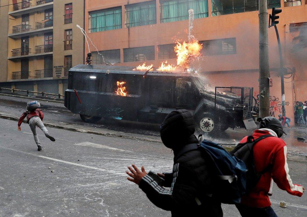 """El Ministerio de Energía ecuatoriano anunció, además, que este lunes se había suspendido las operaciones en tres campos petroleros de la zona amazónica """"debido a la toma de las instalaciones por grupos de personas ajenas"""" a ellas, aseguró un comunicado. En la imagen, un vehículo antidisturbios recibe el impacto de un cóctel mólotov durante las protestas en Quito, este lunes."""