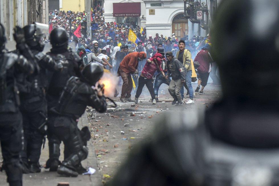 Los manifestantes se enfrentan con la policía antidisturbios mientras miles de personas marchan contra la decisión del presidente ecuatoriano, Lenin Moreno, de recortar los subsidios al combustible, en Quito.