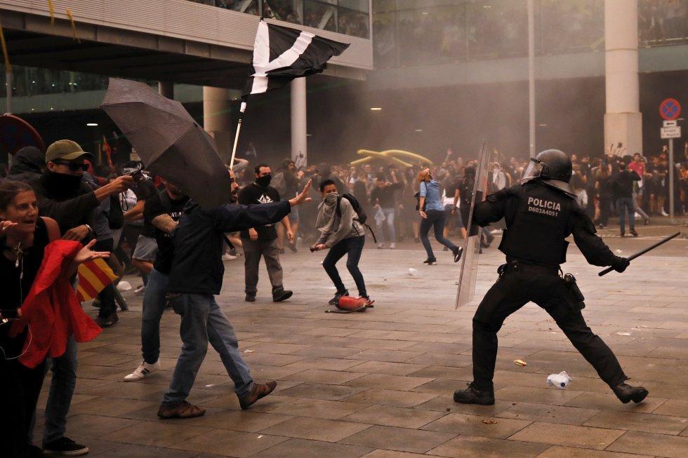 Policías antidisturbios cargan contra los manifestantes en el exterior del aeropuerto de El Prat.