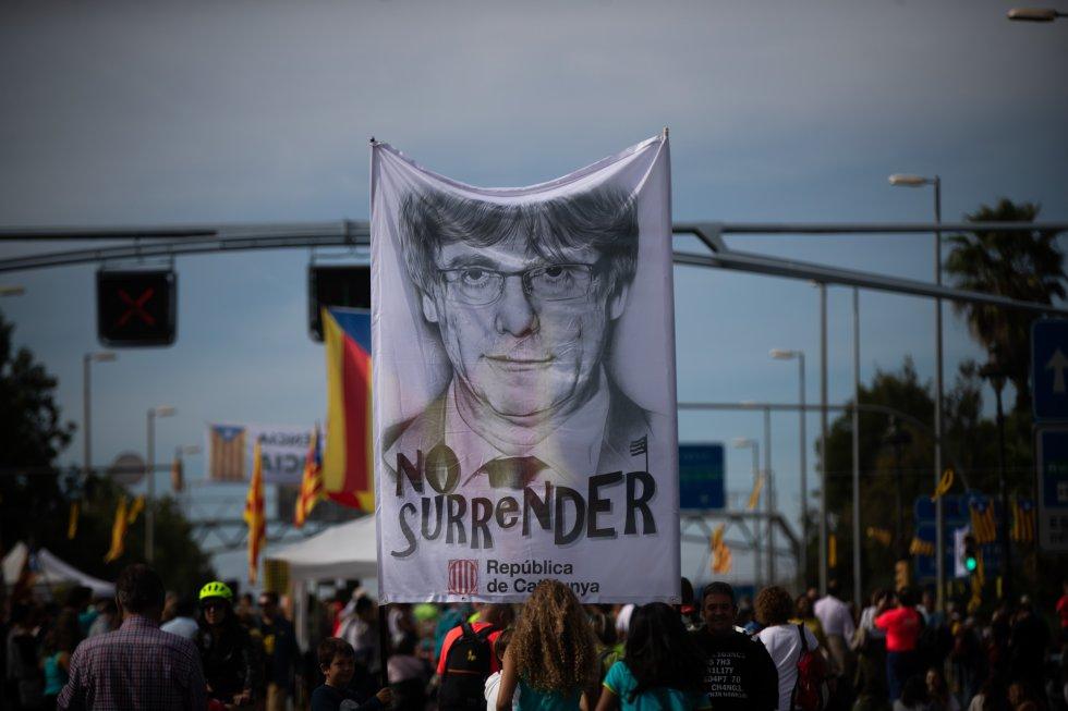 Los integrantes de una de las marchas portan una pancarta con un retrato del expresidente catalán Carles Puigdemont, huido de la justicia en Bélgica, en la que se puede leer 'No surrender' (no rendirse), a su llegada a Barcelona.