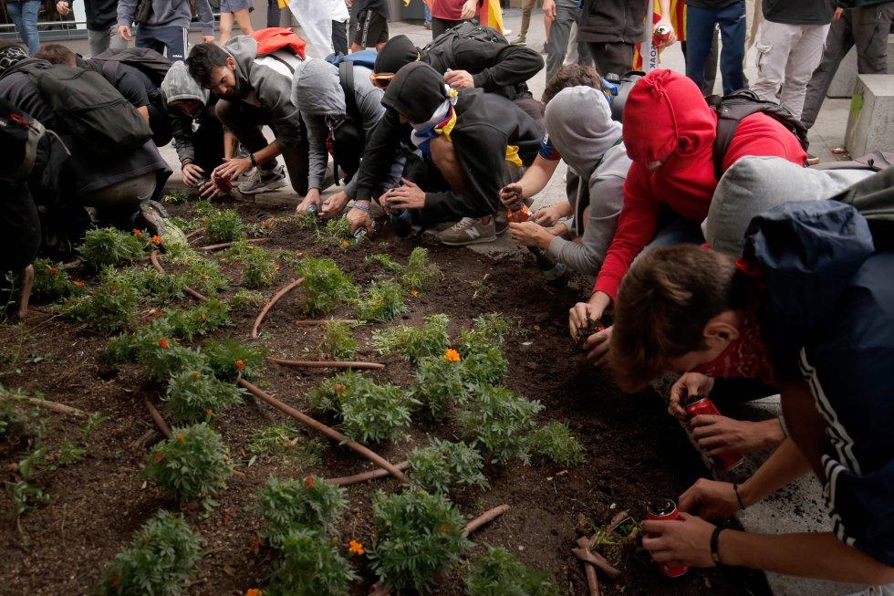 Los manifestantes llenan latas con tierra cerca de una comisaría de la Policía Nacional, en Barcelona.