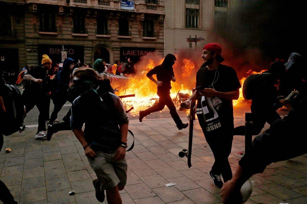 Al menos 26 personas han resultado heridas, una de ellas por contusión ocular, durante las protestas de este viernes contra la sentencia del 'procés' en la capital catalana. En la imagen, manifestantes junto a una barricada durante los enfrentamientos contra la policía en Via Laietana,.