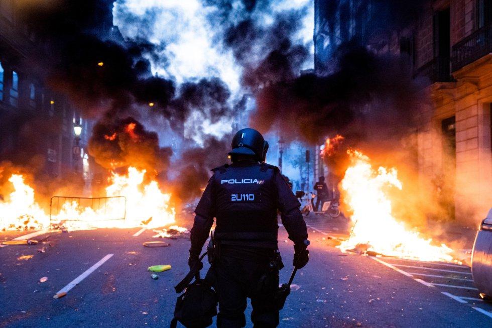 Un policía camina entre barricadas ardiendo cerca de la comisaría de Via Laietana, que ha sido uno de los puntos más conflictivos de la jornada en Barcelona.