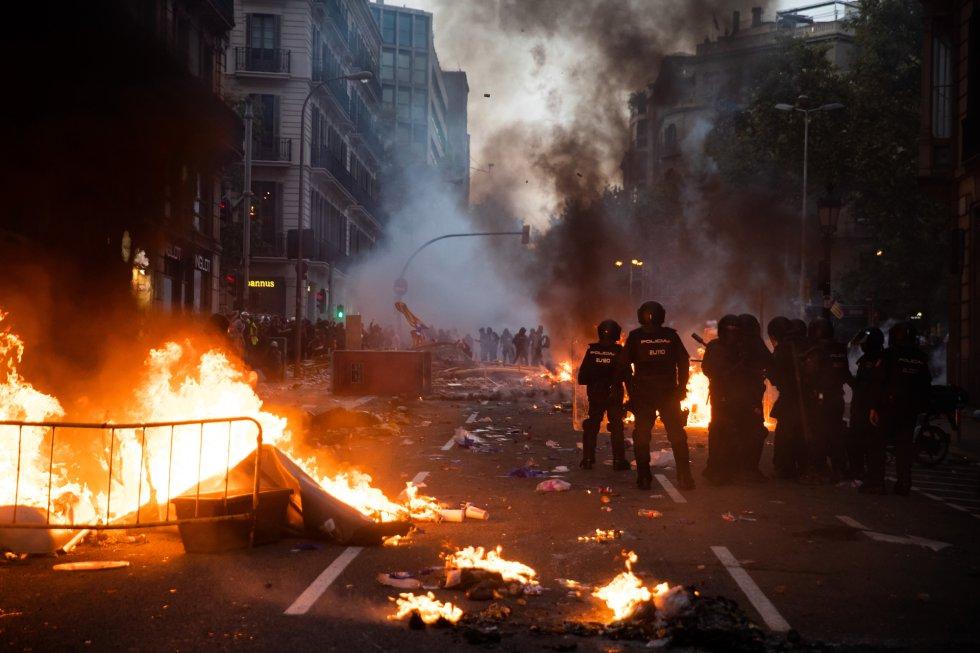 Cataluña vive su quinta jornada de protestas después de que el pasado lunes el Tribunal Supremo dictara la sentencia que condena a penas de entre 9 y 13 años a los líderes del 'procés'. Los altercados han sido especialmente violentos en la capital catalana. En la imagen, enfrentamiento entre manifestantes y policías en el centro de la ciudad, este viernes.