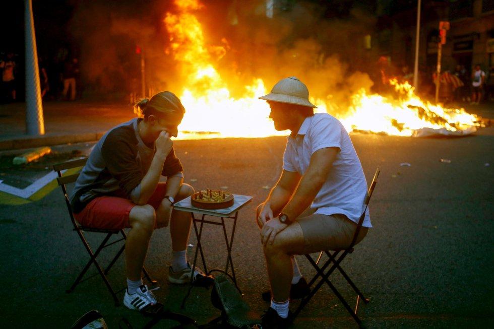 Dos hombres bromean jugando al ajedrez en medio de los disturbios que se están produciendo en Barcelona.