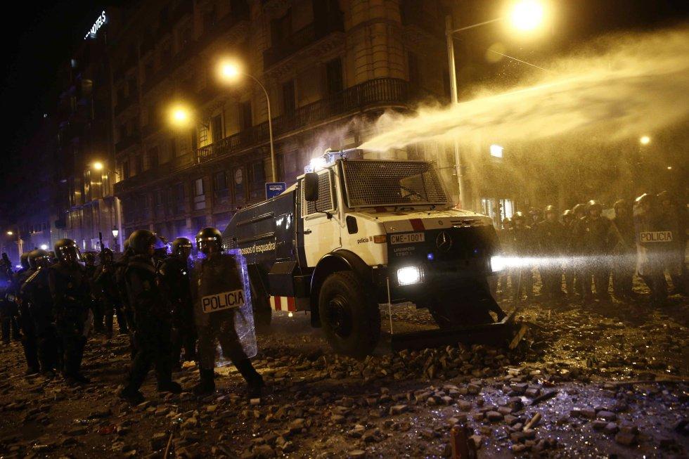 Un grupo de policías antidisturbios junto a la tanqueta de agua a presión durante los altercados que se están produciendo en Barcelona