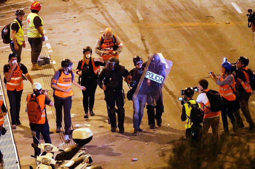 Dos policías detienen al fotoperiodista de EL PAÍS Albert Garcia durante los altercados que se están produciendo en Barcelona.