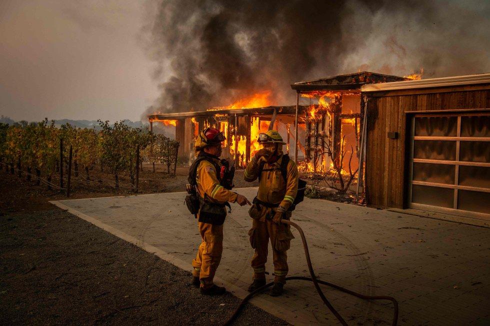 Los cables y transformadores de PG&E que cuelgan por zonas boscosas en todo el norte del Estado están en el origen de los dos incendios más mortíferos en este siglo en California, con más de 100 muertos en los dos últimos años. Décadas de deficiente mantenimiento y mínima inversión en la infraestructura han hecho que, en momentos de especial peligro por las condiciones atmosféricas, no haya otro remedio para prevenir incendios que realizar apagones. En la imagen, bomberos este domingo en Kincade en Healdsburg, California.